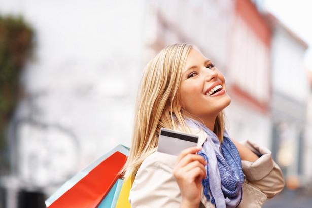 Uśmiechnieta kobieta z zakupami i kartą płatniczą, mat. shutterstock