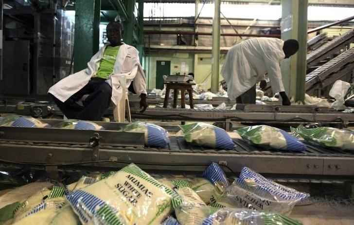 Workers arrange packets of sugar on a conveyor belt at the Mumias sugar factory in western Kenya