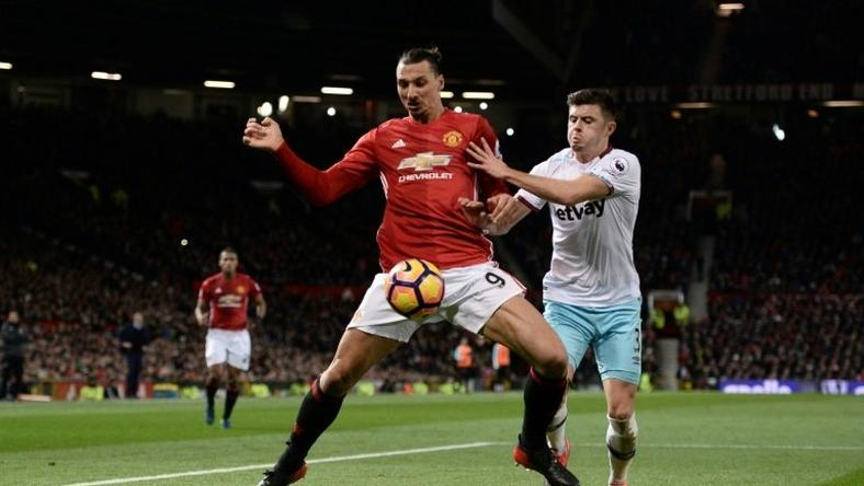 Manchester United's striker Zlatan Ibrahimovic (L) shields the ball from West Ham United's defender Aaron Cresswell (R) during the English Premier League football match between Manchester United and West Ham United on November 27, 2016
