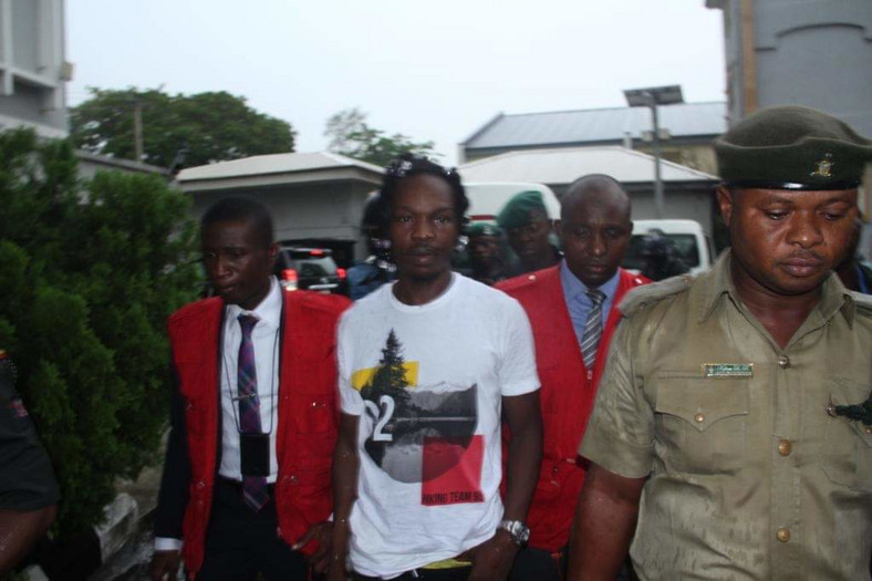 Naira Marley being led to court by men of the EFCC amidst a watertight security. [Twitter/@officialEFCC]