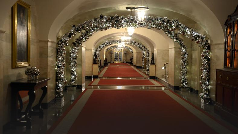 A hallway of the White House features silver arches aglow, a preview of holiday decorations being assembled for the season, in Washington
