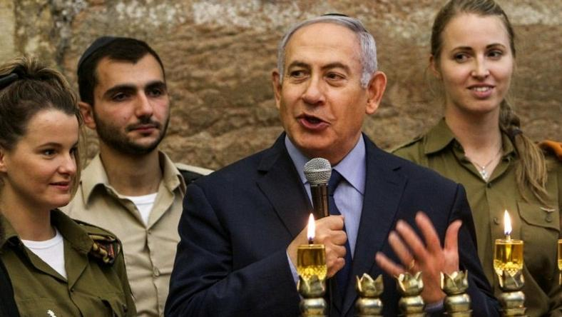 Israeli Prime Minister Benjamin Netanyahu, seen here during a menorah-lighting ceremony with Israeli soldiers for Hanukkah, has hailed majority backing at the UN for condemning militant group Hamas even though a US draft resolution failed to pass