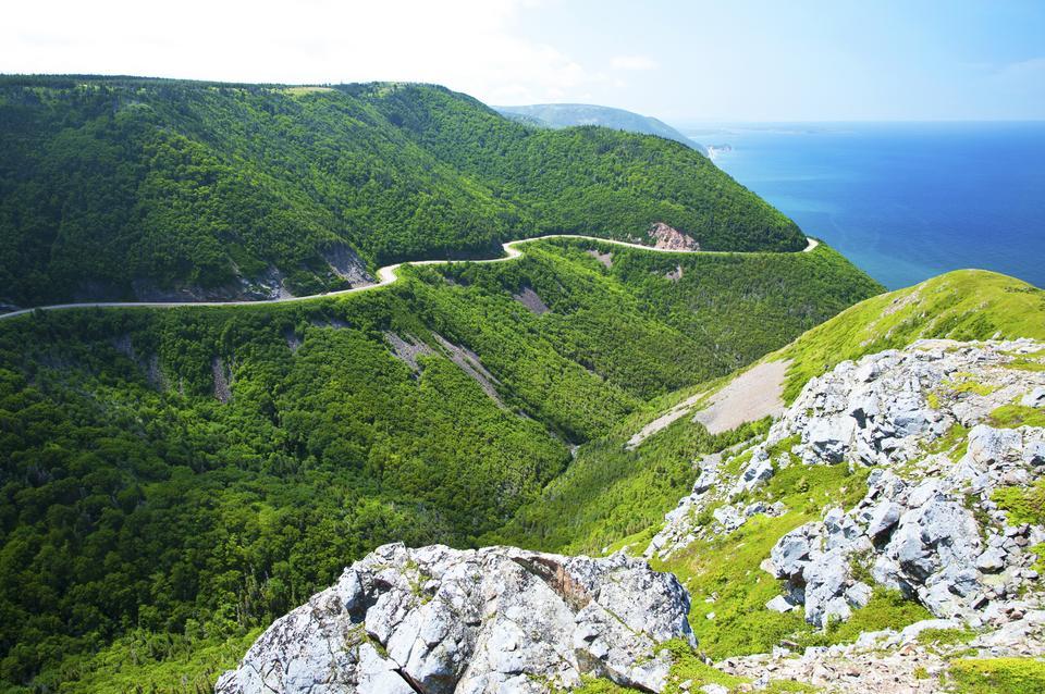 Cabot Trail w Nowej Szkocji w Kanadzie, jest jedną z najbardziej malowniczych tras w kraju. Zabiera kierowców w podróż dookoła części wyspy Cape Breton i prezentuje spektakularne widoki na ocean z licznymi punktami widokowymi, zabytkami i malowniczymi wsiami po drodze. Jeśli możesz, zatrzymaj się na chwilę, możliwe, że zauważysz przepływające wieloryby.