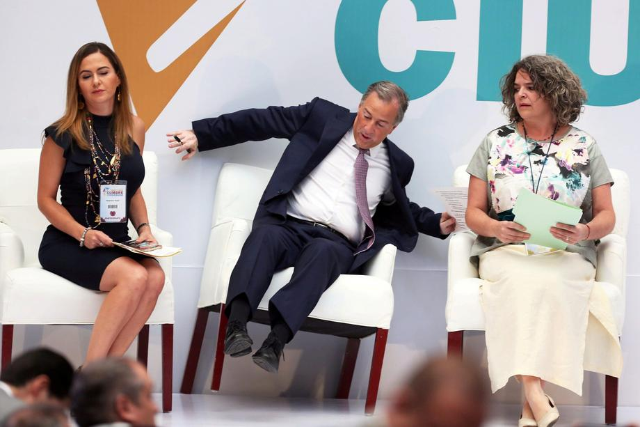 PRI presidential candidate Jose Antonio Meade reacts while falling off his chair after arriving to a