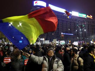 Protester waves Romanian flag during a demonstration in Bucharest