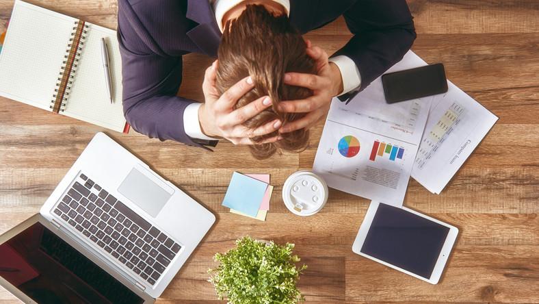 stres zmęczenie pandemia covid praca biuro komputer dokumenty pracownik ból