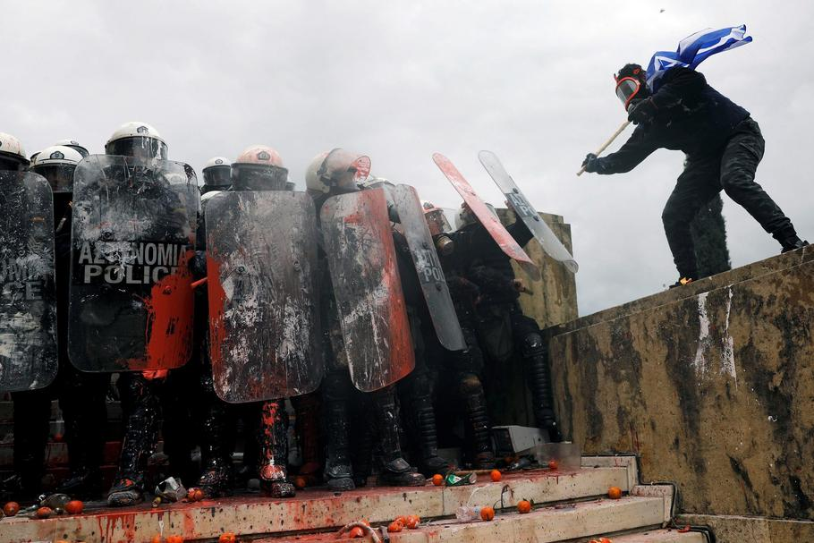 Protesters clash with police officers during a demonstration against the agreement reached by Greece