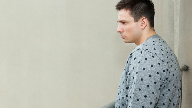 Samotny mężczyzna stoi na balkonie