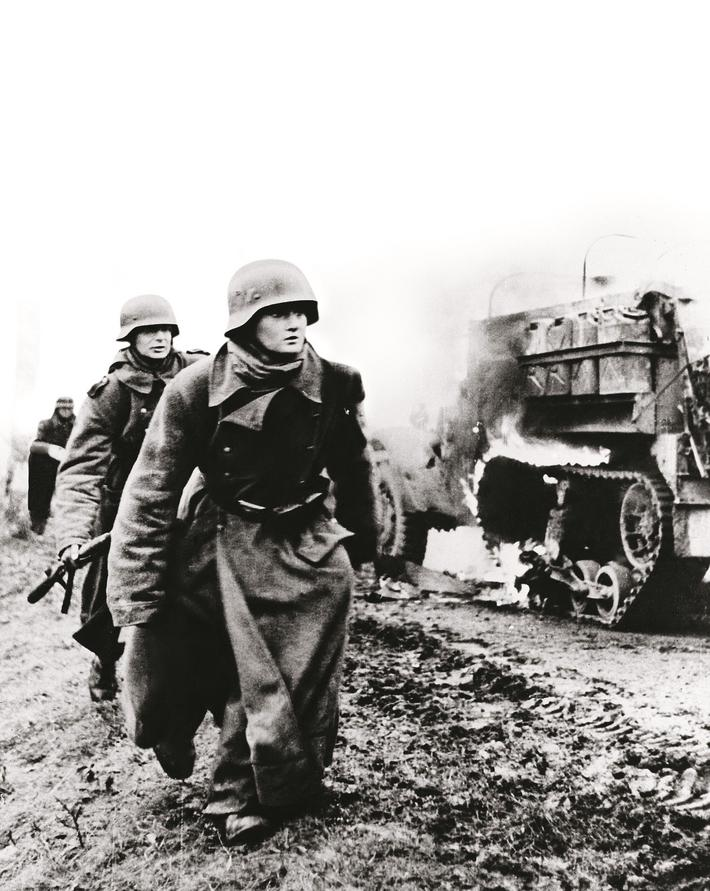 """BATTLE OF THE BULGE, c1944. German troops passing by a burning US Army vehicle as the German infant"