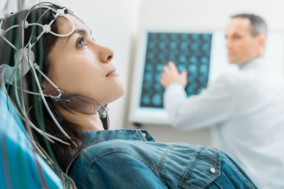 Charming young woman undergoing electroencephalography