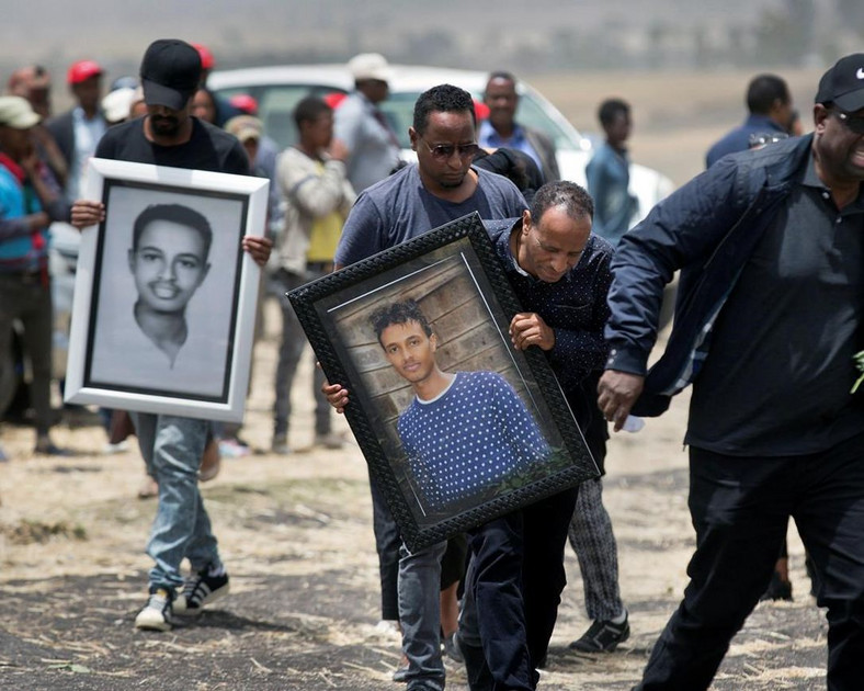 Family members of the flight's main pilot, Captain Yared Getachew, carry photographs of him. (Toronto Star)