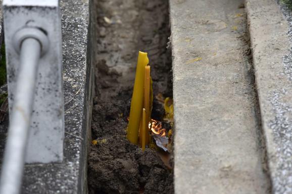 Upaljene sveće nakon što je pop ponovo osveštao grob