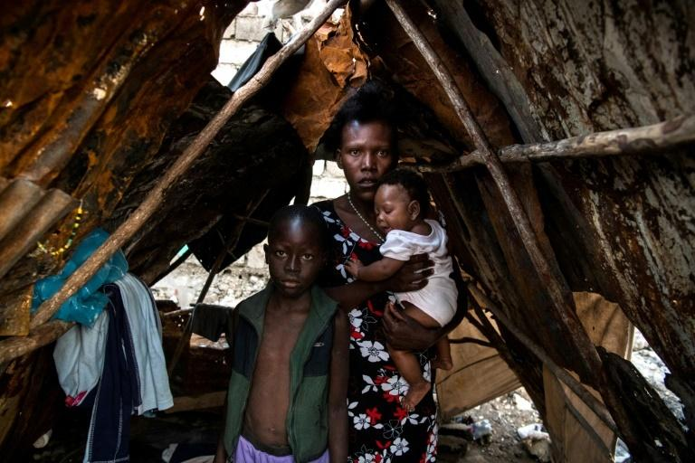 Etienne, 10, Jolande Baptiste, 27, and Lenia Cha, 4 months, pose inside a makeshift shelter on the site of their home which was burned during a November 2018 gang war in Port-au-Prince