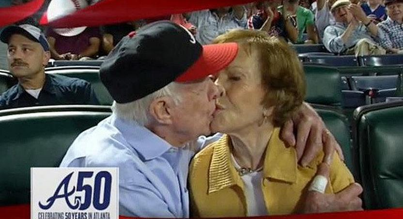 """Former President Jimmy Carter kisses his wife Rosalynn on the """"Kiss Cam during a baseball game between the Atlanta Braves and the Toronto Blue Jays on Sept. 17, 2015"""