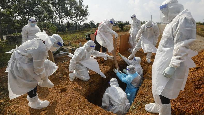 Ochotnicy w kombinezonach ochronnych zakopują ciało ofiary COVID-19 w Malezji