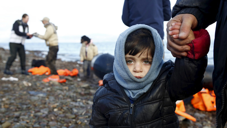 A Syrian refugee child looks on, moments after arriving on a raft with other Syrian refugees on a beach on the Greek island of Lesbos