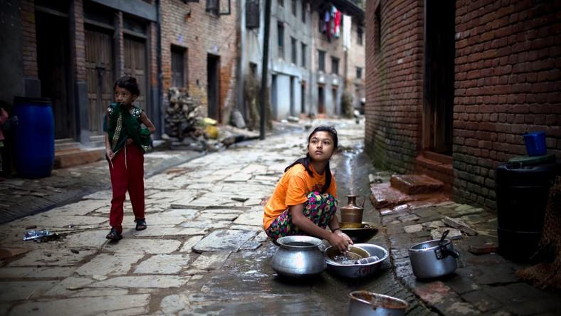 Nepal. Dziewczynka myje naczynia na ulicy osiedla Khokana na przedmieściach Katmandu