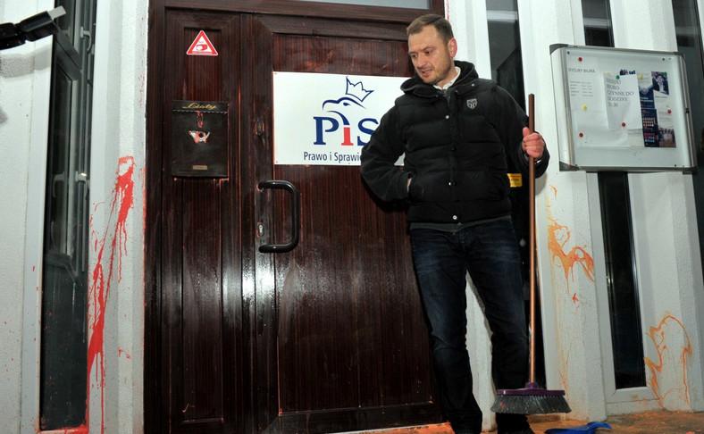 Poseł PO Sławomir Nitras zmywa farbę z drzwi biura PiS w Szczecinie