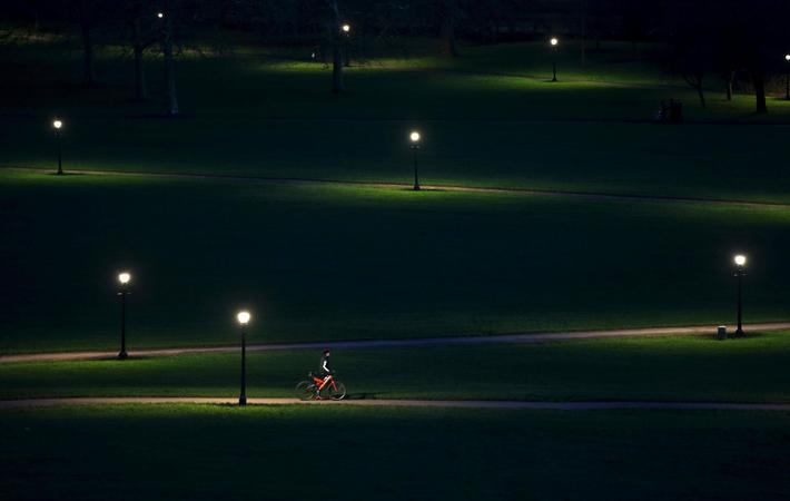 A cyclist rides through Primrose Hill in the early evening in London