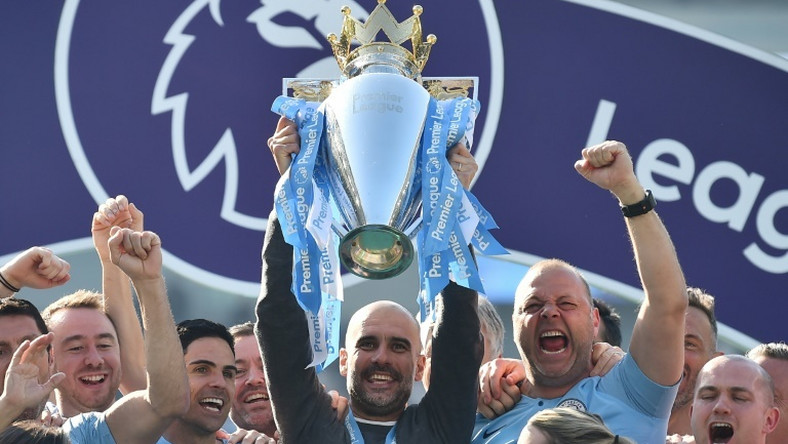 Manchester City manager Pep Guardiola holds up the Premier League trophy