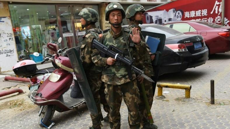 Chinese paramilitary police stand guard outside a shopping mall in the western Xinjiang region in 2015