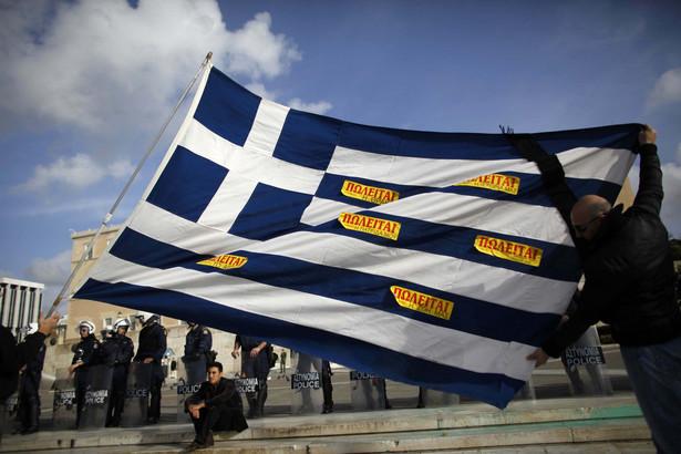 """Protestujący Grecy z flagą swojego kraju obklejoną kartkami z napisem """"na sprzedaż""""."""