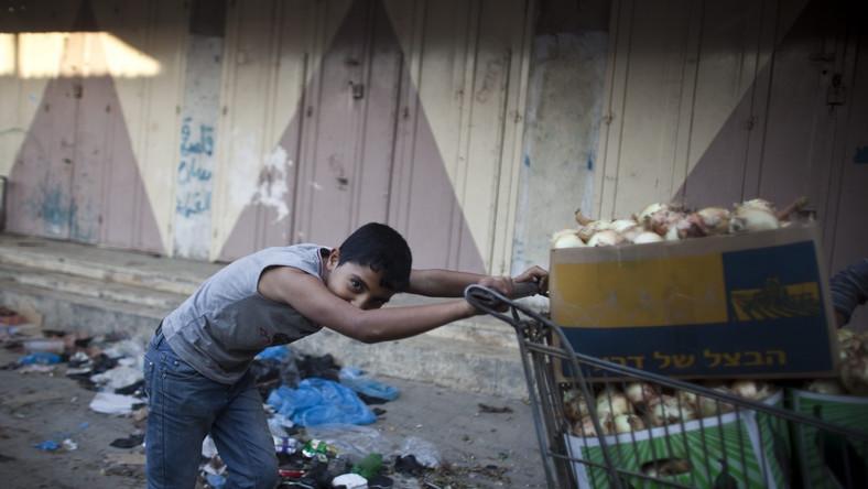Młody Palestyńczyk pcha wózek z cebulą w drodze na targ w obozie dla uchodźców w Jabalii