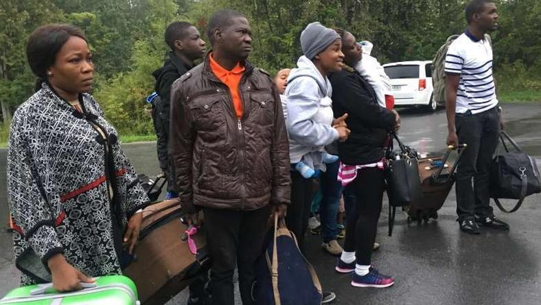 Asylum seekers who are steps away from Canada listen as the Royal Canadian Mounted Police tells them they will be arrested as they cross over from New York state, north of Plattsburgh