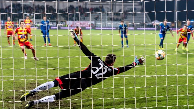 Piłkarz Jagiellonii Białystok Guilherme Sitya (L) pokonuje z rzutu karngego Antona Kanibołockiego (C) z Miedzi Leginica