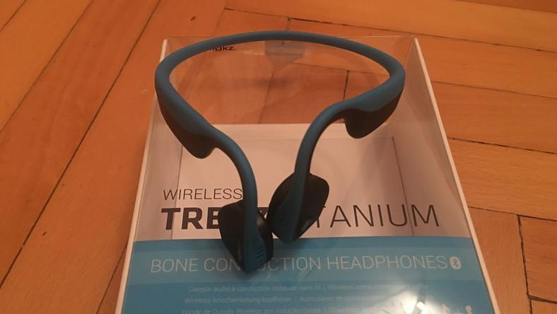 """Trekz Titanium to słuchawki bezprzewodowe przeznaczone dla ludzi aktywnie uprawiających sport. W przeciwieństwie do tradycyjnych modeli, tu dźwięk nie trafia do uszu, a słuchawki dotykają naszej kości policzkowych i przez """"przewodnictwo kostne"""" dźwięk trafia do naszego mózgu. Jakość dźwięku jest średnia, do tego nie ma mowy o żadnej izolacji - w pociągu czy w bibliotece lepiej ich nie używać. Za to, dla osób ćwiczących na zewnątrz, czy jadących na rowerze te wodoodporne słuchawki oferują rzecz, której konkurencja nie ma - odkryte uszy, dzięki czemu nie ominie nas choćby dźwięk nadjeżdżającego samochodu. Idealnie też sprawdzają się w czasie rozmowy telefonicznej. Cena? Ok 130 dolarów"""