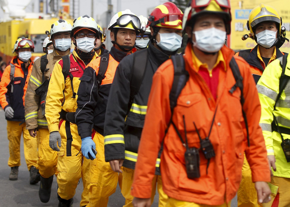 Rescue personnel walk to the site where a 17-storey apartment building collapsed in an earthquake in Tainan
