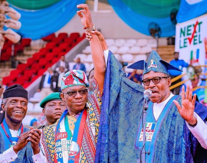President Muhammadu Buhari (right) raises the hand of Dapo Abiodun (centre) with Vice President Yemi Osinbajo (left) looking on. Chaos ensued shortly after [Twitter/@raufaregbesola]