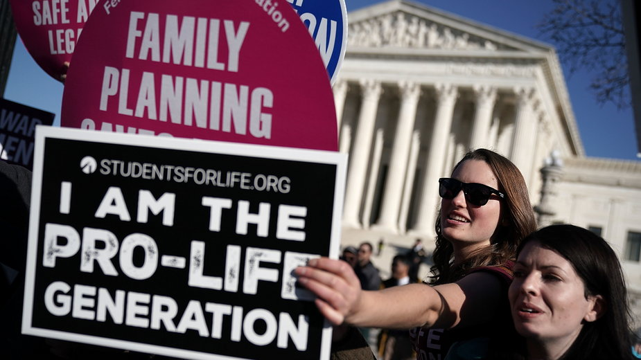 Aktywistki pro-life zasłaniają plakat aborcyjny podczas Marszu dla życia, Waszyngton