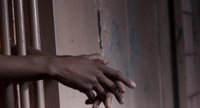 Hands gripping the bars of a jail cell