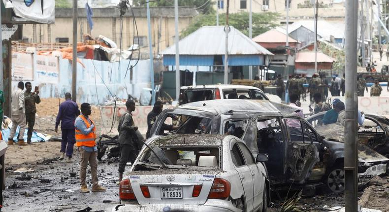 Civilians and Somalian security officers gather at the scene of a suicide car bomb at a street junction near the president's residence, in Mogadishu, Somalia, September 25, 2021. REUTERS/Feisal Omar