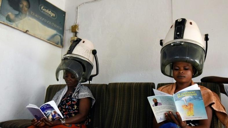 Women sitting under hair steamers read books from a mini-library at a hairdresser's in Abidjan