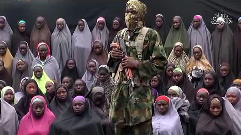 A masked gunman stands in front of a group of girls in a Boko Haram video released on August 14, 2016 purporting to show the Chibok hostages (Capital FM)