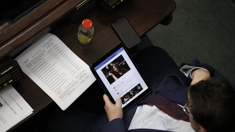5 Posiedzenie Sejmu X Kadencji. Jeden z posłów przegląda newsy o geście Joanny Lichockiej