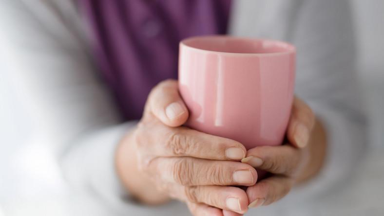 Starsza kobieta trzyma kubek