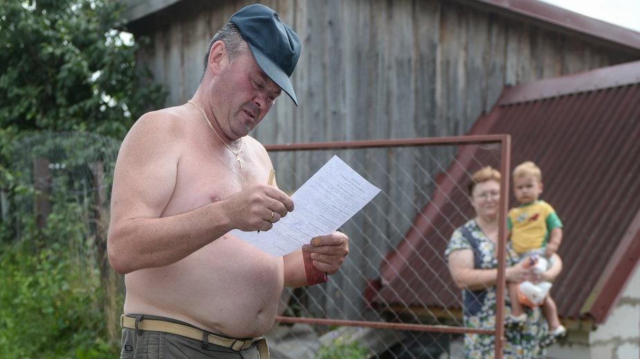 Białoruski wyborca czyta kartę do głosowania. W mniejszych miejscowościach wyborcy głosują w ruchomych komisjach wyborczych (9 sierpnia 2020 r.)