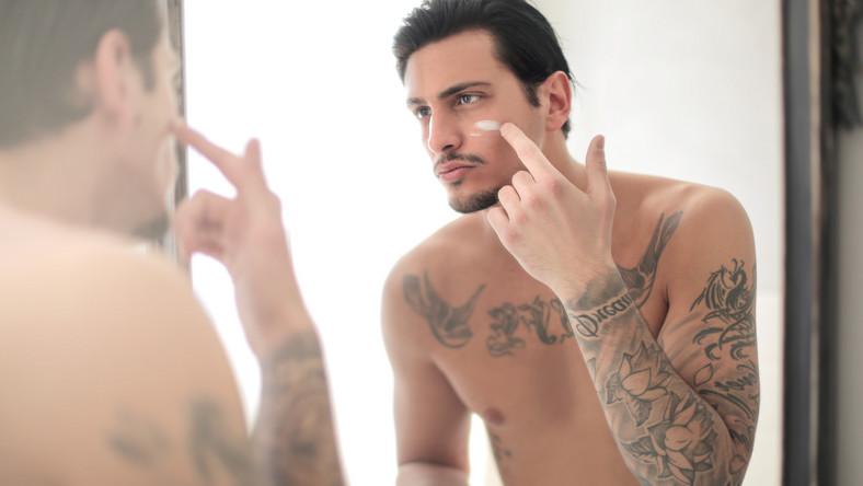 Mężczyzna smaruje sobie twarz kremem