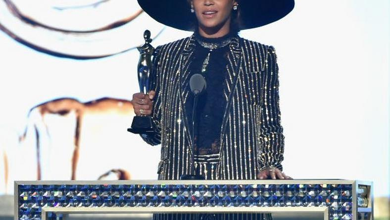 Beyonce receives the 2016 CFDA Fashion Icon Award in a shimmering Givenchy suit and hat