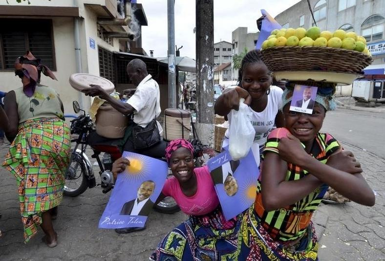 Street vendors hold campaign posters for presidential candidate Patrice Talon ahead of the second round of Benin's presidential election on Sunday in Cotonou, Benin, March 18, 2016. REUTERS/Charles Placide Tossou