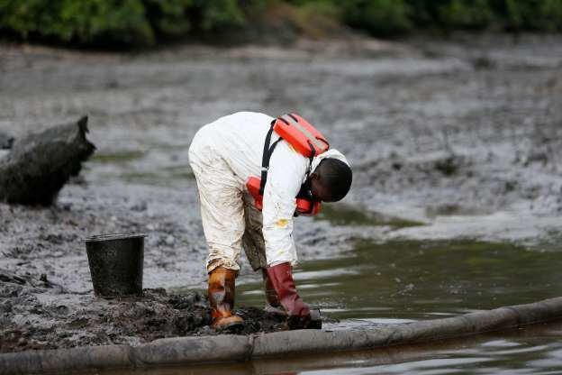A man scoops recovered crude oil retained behind the boom at the Bodo clean-up in Rivers State, Nigeria (AFP)