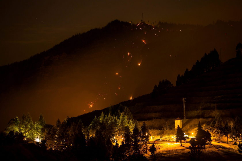 Flames and smoke from a forest fire are seen in the village of Valleseco