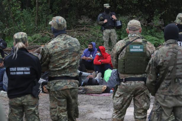 Grupa uchodźców i straż graniczna w pobliżu miejscowości Usnarz Górny k. Krynek
