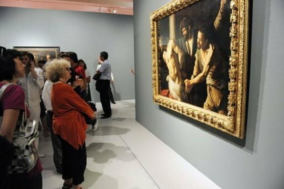 Posetioci izložbe posmatraju jednu Karavađovu sliku