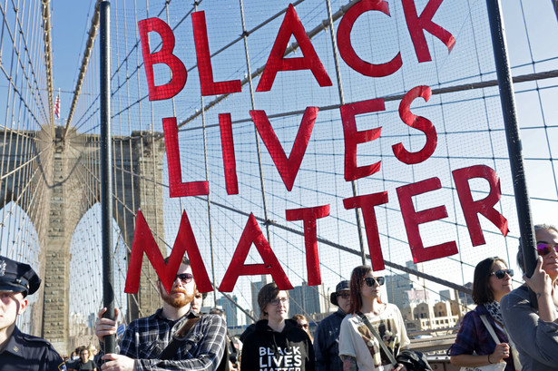 """Demonstrators hold a """"Black Lives Matter"""" banner while participating during the March for Racial Justice on the Brooklyn Bridge in the Brooklyn borough of New York, U.S., on Sunday, Oct. 1, 2017. The March for Racial Justice is a multi-community movement organized to protest against systemic racism and promote civil rights for all. Photographer: Yana Paskova/Bloomberg"""