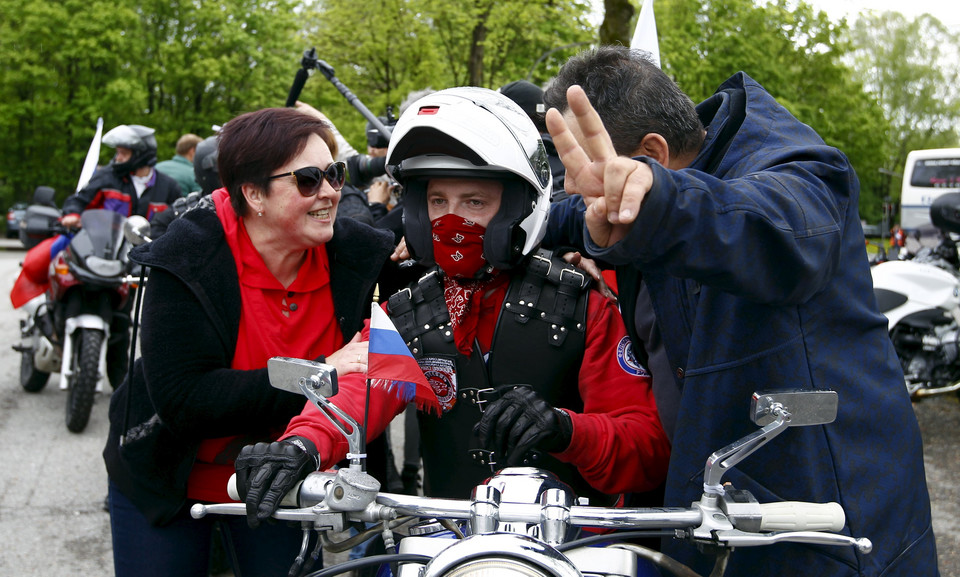 People pose with a member of the Russian motorcycle group called 'Nachtwoelfe' at the parking space of the former German Nazi concentration camp in Dachau