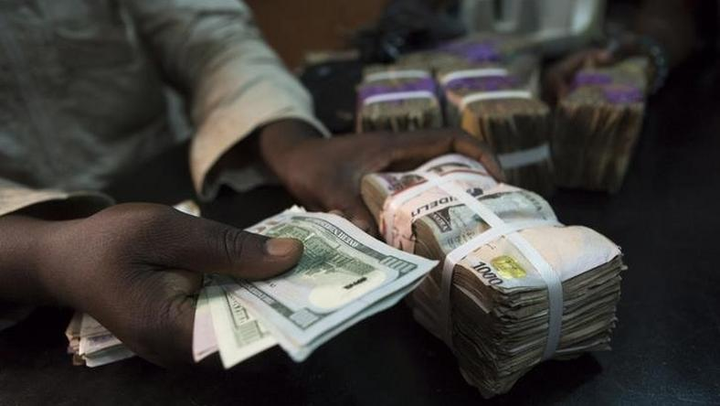 A trader changes dollars with naira at a currency exchange store in Lagos February 12, 2015.